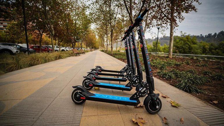 Muestra un grupo de scooters eléctricos en un área peatonal.